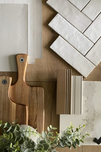 Flat lay with a natural woods and greiges showing herringbone subway tile.